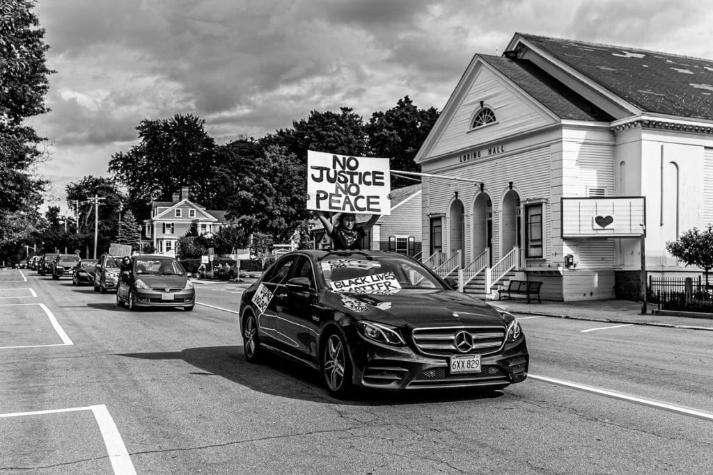 Rohini Gajaraj, holding a sign in the first car during the June 7 car caravan rally. Photo by Brooke Bartletta.