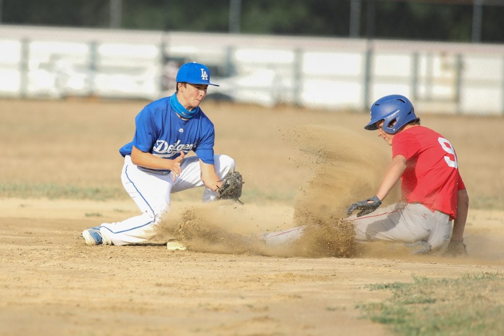The Cardnials' James Rozanitis slides under the tag of Dodgers' SS Teddy Swanson during the championship game. (Photo by Joshua Ross Photography)