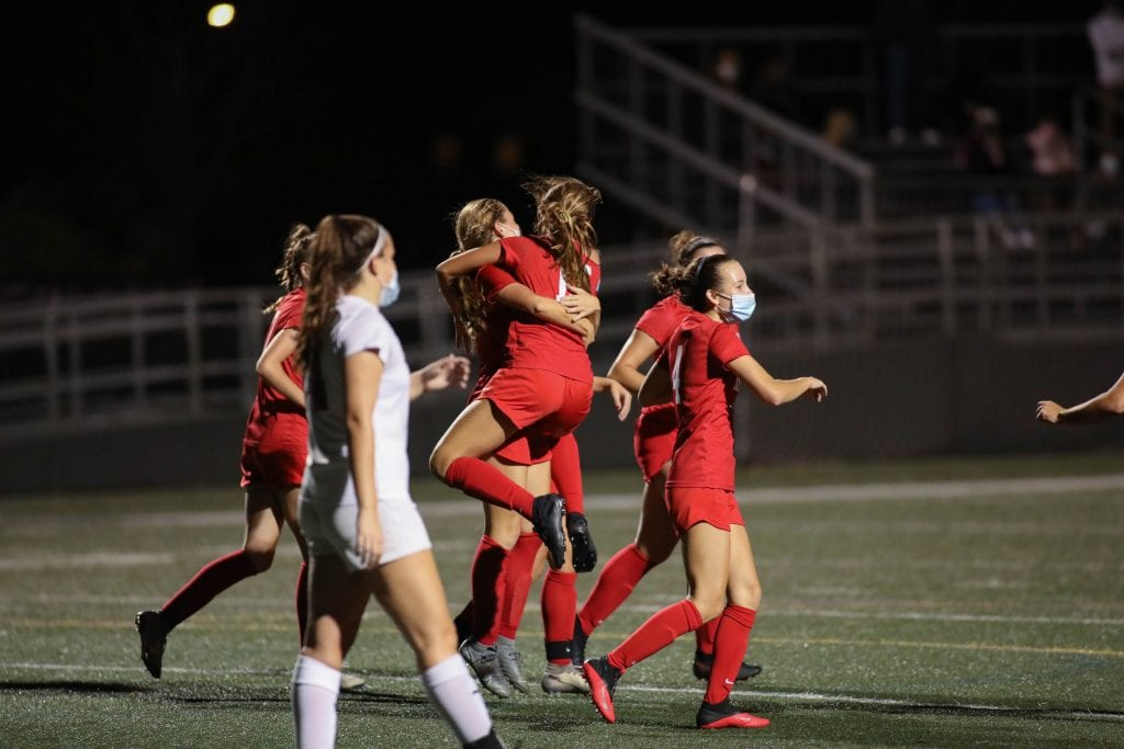 Junior captain Alexa Varholak jumps into her sister Ava's arms after her younger sibling scored in the the 3rd quarter.
