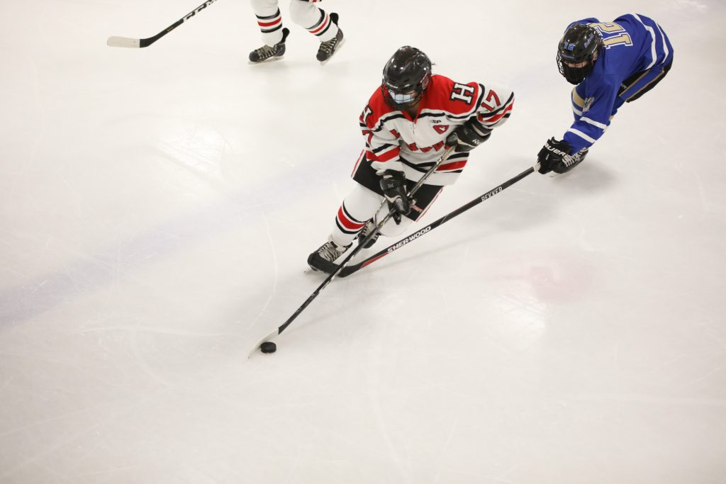 Senior captain Coco Hernberg skates by a Norwell defender.