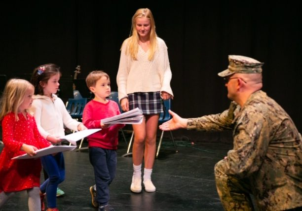 "From left, Derby Academy Pre-Kindergarteners Kathryn Mountcastle, of Scituate, Riley Carter, of Cohasset, and Cooper Mathien, of Hingham, join Grade 8 student Georgia Barrett, of Hingham, in presenting ""thank-you"" cards to Hingham Director of Veterans' Services Senior Chief Petty Officer Keith Jermyn of the United States Navy during a special Veterans Day presentation at Derby Academy in Hingham,  Friday, November 1, 2019."
