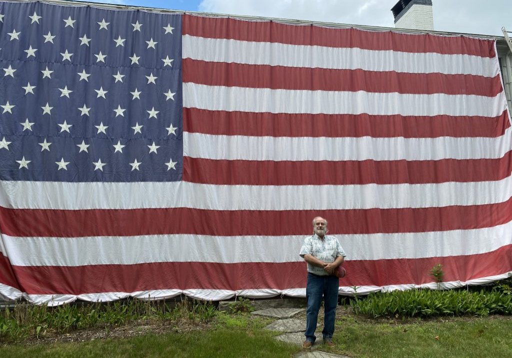 "Gerry Earle in front of the ""Flag House"" Photo by Anchor staff."